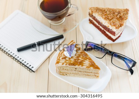 Prepare writing in coffee shop, Booklet and delicious cake on a wooden table - stock photo