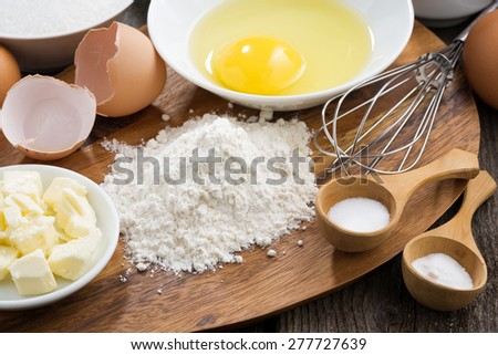 prepared baking ingredients on a wooden board, close-up - stock photo