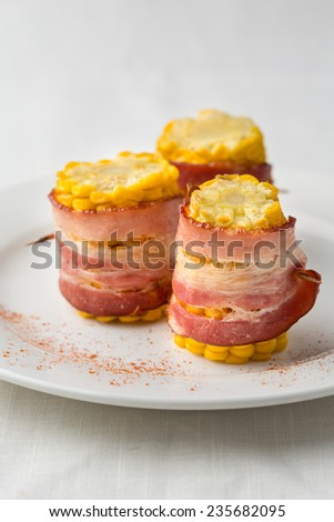 prepared corn pieces with bacon on white plate - stock photo