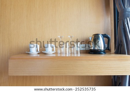 prepared cup , glass and electric kettle on wood shelf in luxury hotel room. - stock photo