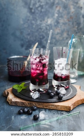 Prepared Fresh blueberry drink with ice cubes in glasses. - stock photo
