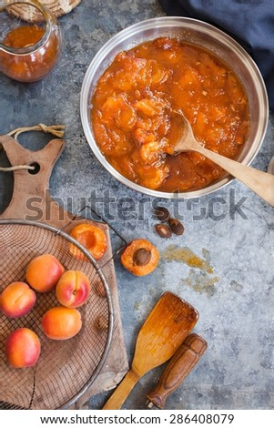 Prepared homemade orange apricot jam over on kitchen rustic table with rustic utensils and tools. Top view. Rustic style.  - stock photo
