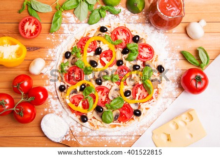 Prepared Italian pizza with sauce, tomato and other ingredients other on the wooden background  - stock photo