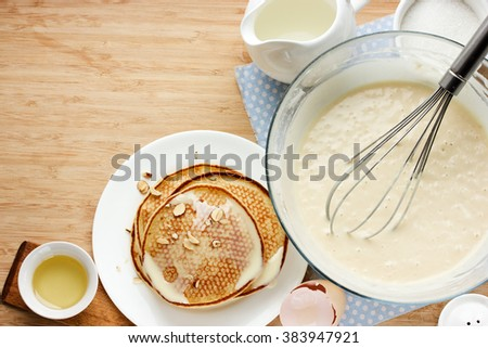 Prepared pancakes for breakfast. Ingredients for making pancakes, dough and fried pancakes on a wooden table. Top view with free text space - stock photo