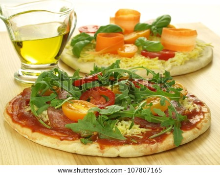 Prepared pizzas with vegetables and tomato sauce - stock photo