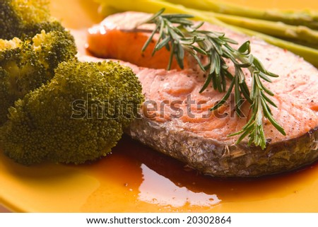 Prepared salmon steak with broccoli and asparagus on yellow plate - stock photo