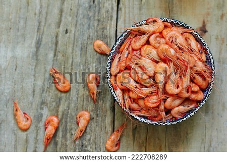 Prepared shrimp on blue plate on wooden background - stock photo