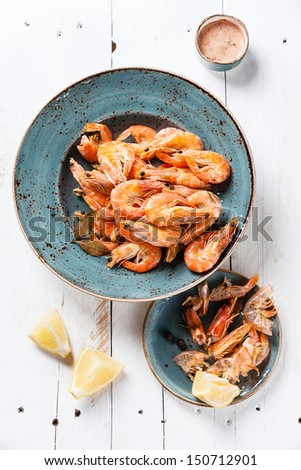Prepared shrimps on blue plate on wooden background - stock photo