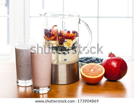 Prepared smoothies and healthy smoothie ingredients in blender with fresh fruit ready to blend on kitchen table - stock photo
