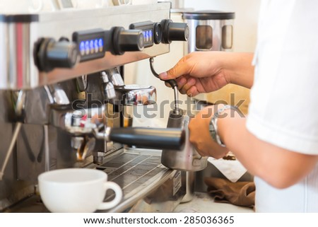 Prepares espresso in coffee shop - stock photo