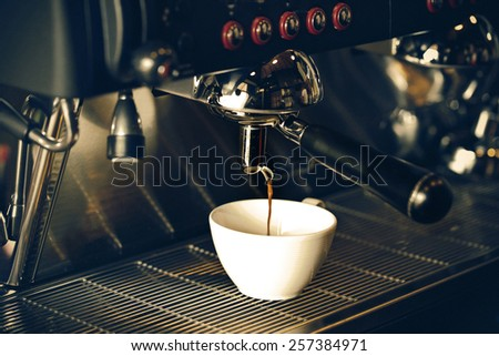 prepares espresso in his coffee shop; close-up - stock photo