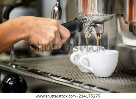 prepares espresso in his coffee shop with hand and close up - stock photo