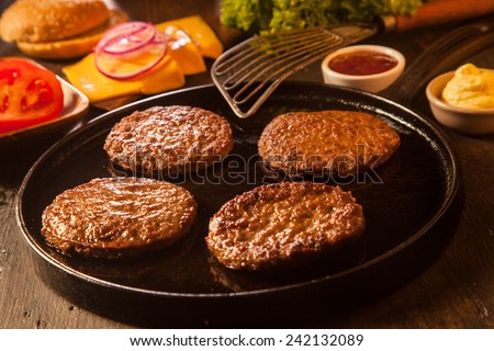 Preparing a batch of cheeseburgers with assorted ingredients and four grilled ground beef patties or frikadeller in a pan - stock photo