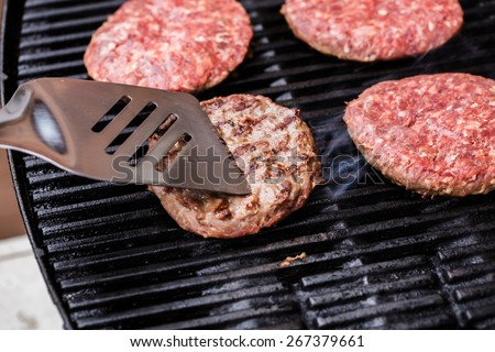 Preparing a batch of ground beef patties on grill or BBQ with one of them on spatula - stock photo