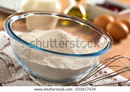 Preparing a dough/batter for crepes or pancakes with wheat flour in glass bowl, milk, eggs and oil in the back and a beater on the side (Selective Focus, Focus one third into the bowl)