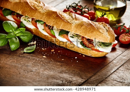 Preparing a fresh crusty baguette with Caprese filling in the kitchen with fresh basil leaves, cherry tomatoes, olive oil and mozzarella cheese - stock photo