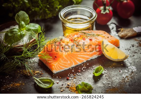 Preparing a gourmet salmon meal with a thick succulent fish fillet, olive oil, herbs, spice rub and seasoning on a kitchen counter, close up view - stock photo