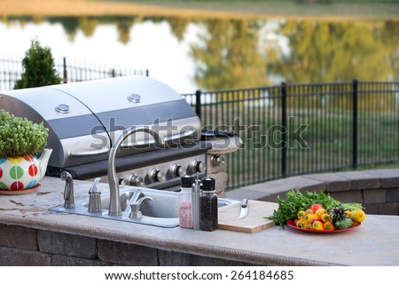 Preparing a healthy summer meal in an outdoor kitchen with gas barbecue and sink on a brick patio overlooking a tranquil lake with tree reflections - stock photo