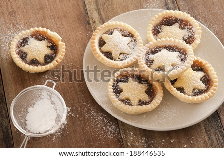 Preparing a plate of delicious Christmas mince pies decorated with pastry stars and sprinkling them with icing sugar from a sieve in a country kitchen on a wooden counter, high angle view - stock photo