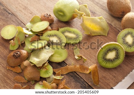 Preparing a tropical kiwifruit dessert with a high angle view of peels, peeled kiwi fruit and sliced fruit being prepared in a rustic country kitchen - stock photo