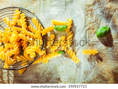 Preparing an Italian fusilli pasta dish with fresh basil leaves and the traditional spiral corkscrew shaped pasta lying in an old retro wire strainer on grunge crumpled paper outdoors in the sunshine - stock photo