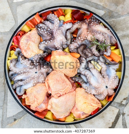 Preparing and Cooking of octopus and chicken in traditional Balkan Greek Mediterranean meal Peka in metal pots called sac sach or sache or a lid. Traditional roast of octopus with potatoes and onions  - stock photo