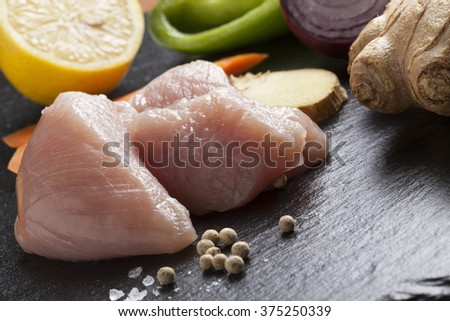 preparing asian food cooking ingredients chicken and vegetables on black slate plate - stock photo