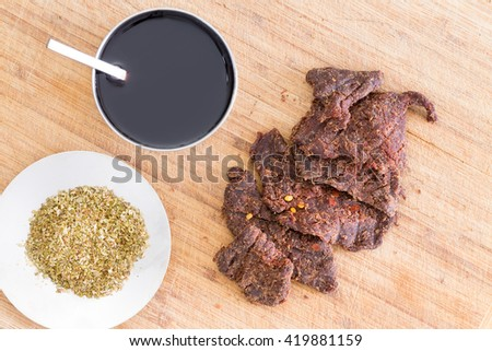 Preparing beef jerky for drying with strips of lean beef, dried oregano and teriyaki sauce on a kitchen cutting board viewed close up from above - stock photo