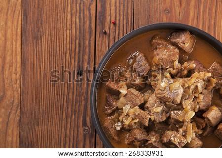 Preparing beef stew - wooden background - stock photo