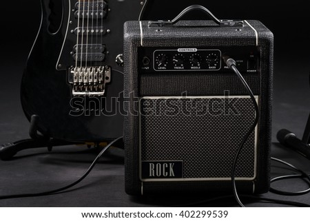 Preparing before a rock concert by getting ready musical instruments. Connected electric guitar to its special black amp. Dark background in studio. - stock photo