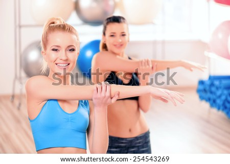 Preparing bodies to summer season. Two beautiful young women in sports clothing exercising together and smiling at camera while standing in sports club  - stock photo