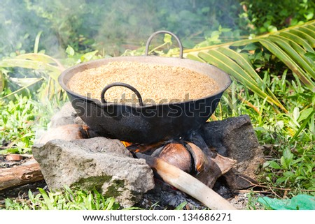 Preparing/boiling paddy in a rural village in Sri Lanka in order to get rice for household use. - stock photo