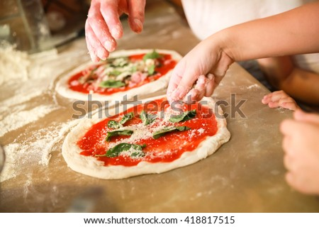 Preparing Classical Pizza Margherita. Cooks add grated parmesan cheese. Selective focus