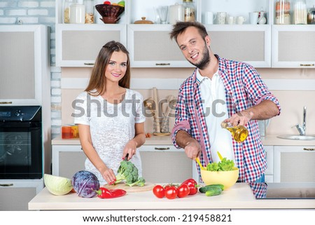Preparing cooking a salad. Young and beautiful couple in love looking at each other while preparing dinner with vegetables in the kitchen. - stock photo