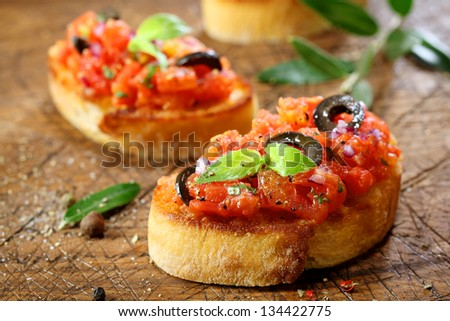 Preparing delicious Italian tomato bruschetta with chopped vegetables, herbs and oil on grilled or toasted crusty baguette sprinkled with seasoning and spices on an old grungy wooden chopping board - stock photo