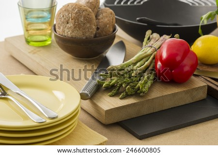 Preparing dinner with fresh vegetables in the kitchen with a bunch of green asparagus spears and a colorful red sweet bell pepper on a chopping board with plates and rolls - stock photo