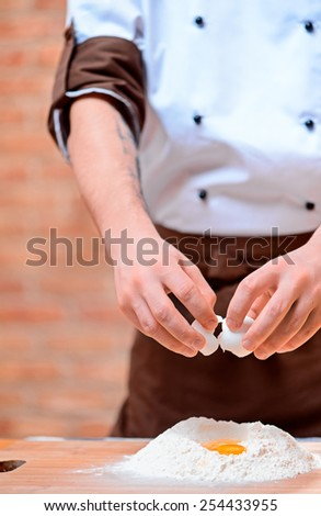 Preparing dough for pastry. Closeup image of cook in uniform cracking eggs upon flour on wooden cutting board in bakers kitchen - stock photo