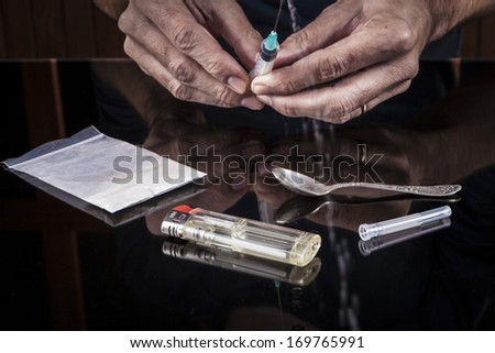 Preparing drugs in a syringe on dark background with reflection - stock photo