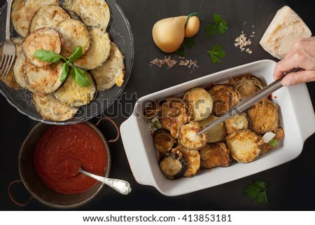 Preparing eggplant parmigiana, fourth step, cook hand with tongs adding another fried eggplant slices layer above the mozzarella and parmesan layer. - stock photo