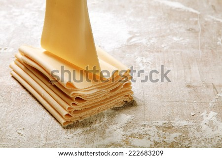 Preparing Folded Fresh Egg Flat Pasta on Wooden Table Filled with Flour. - stock photo