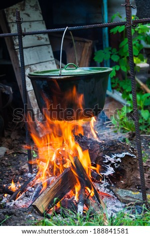 Preparing food in wilderness, baking sausage on fireplace - stock photo