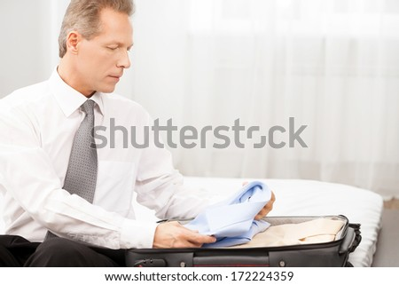 Preparing for business trip. Confident grey hair man in shirt and tie packing his luggage while sitting on the bed - stock photo