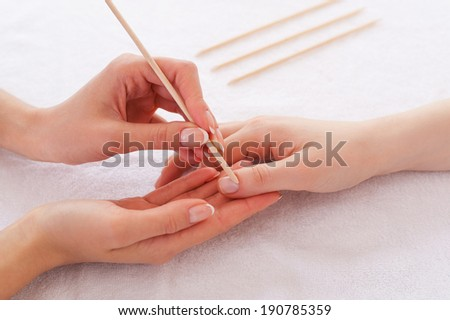 Preparing for manicure. Close-up of beautician cleaning nails of female customer - stock photo