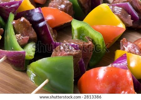 Preparing fresh beef steak shishkabobs with vegetables - stock photo
