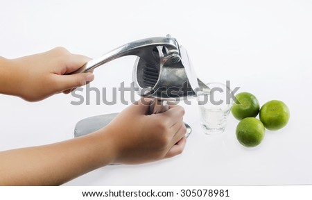 Preparing fresh lemon juice squeezed with stainless juicer on white background - stock photo