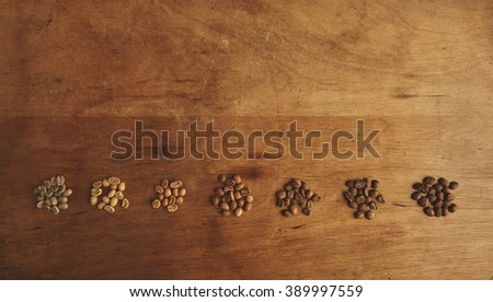 Preparing fresh roast coffee beans to brew with top view of seven different grades of roasting beans in row line on a weathered driftwood background - stock photo