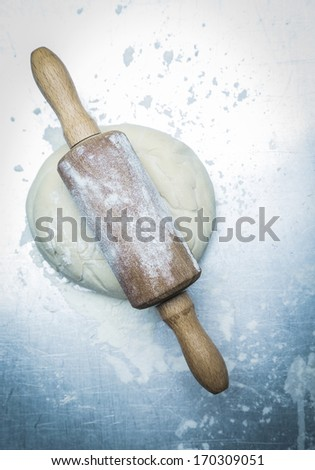 Preparing homemade Italian pizza with an overhead view of an old wooden rolling pin on flattened dough ready for the base or pie crust - stock photo