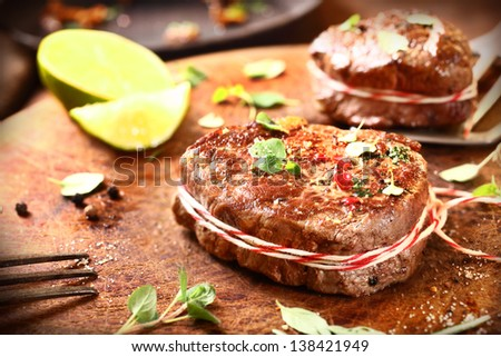Preparing medallions of thick succulent grilled beef steak tied with string and seasoned with fresh herbs and spices on an old wooden chopping board in the kitchen - stock photo