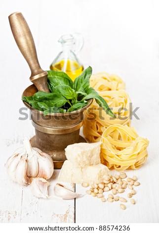 Preparing pesto in mortar on white wooden background - stock photo