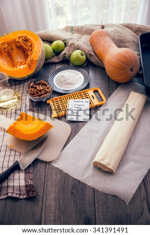 Preparing pie with pumpkins on wooden table - stock photo